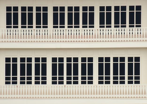 白いコンクリートの建物で古典的な木製の窓