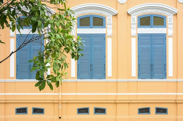 淡いオレンジ色のコンクリートの建物で古典的な青い木製の窓