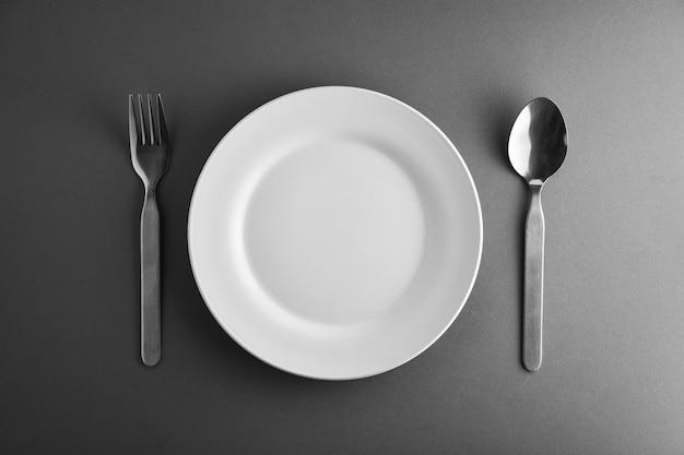 フォーク、スプーン、そして白いセラミック皿