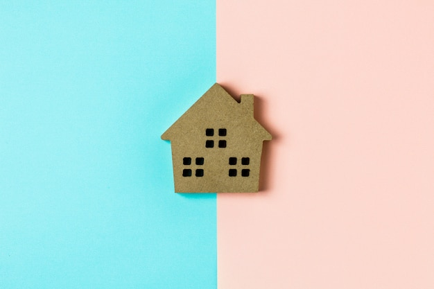 青とピンクの背景に茶色の木の家のアイコン