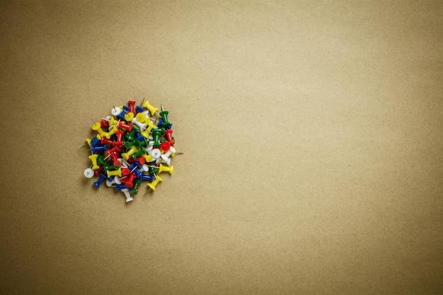 茶色のリサイクル紙の背景に押しピンの山。