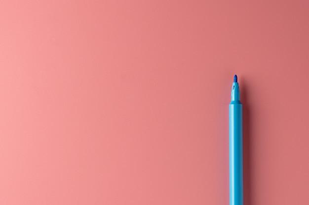 ピンク色の背景に青い色のペン。