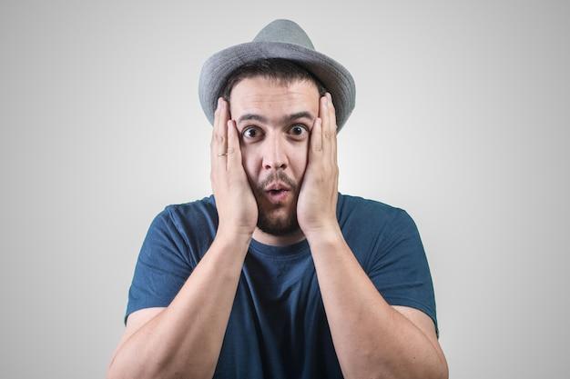 Человек в шляпе удивлен руками на лице