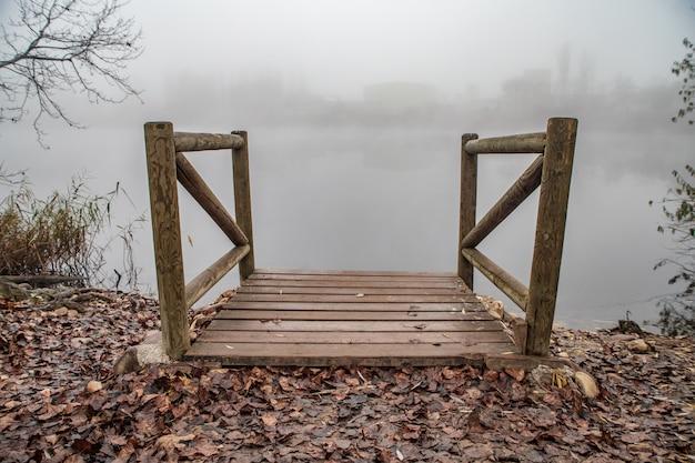 霧の湖の上の木製の桟橋