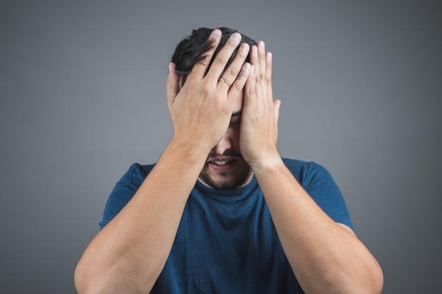 頭痛を持つ男は、彼の顔に彼の手を置く