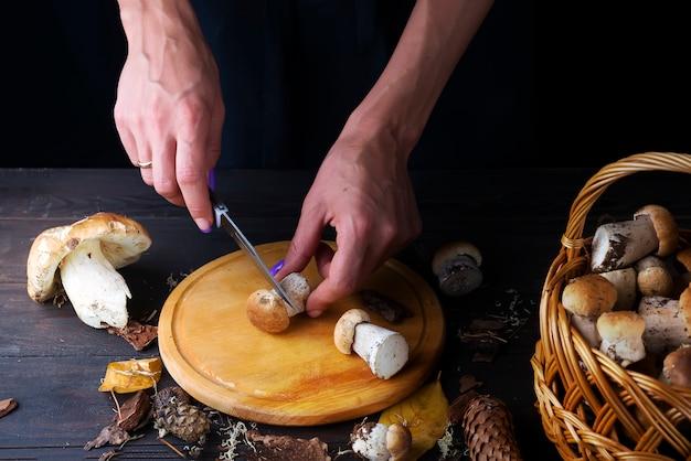 女性の手がキッチンボードにキノコを切る