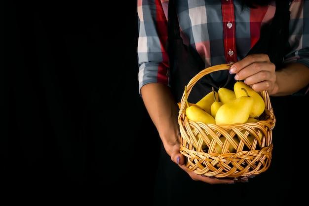 女性の手は梨のバスケットを保持します