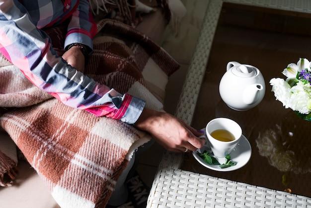 女性はお茶を一杯持っています。
