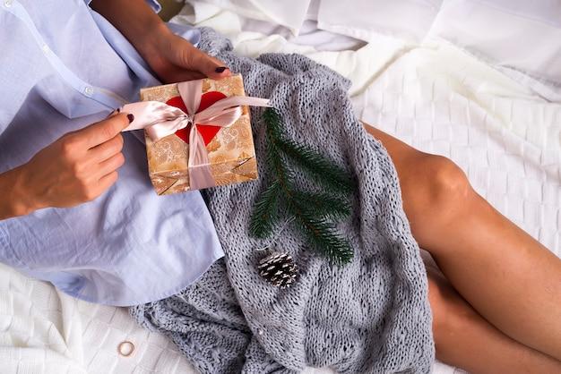 Девушка на кровати держит подарок