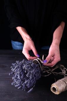 Женщина создает букет из натуральных цветов лаванды,