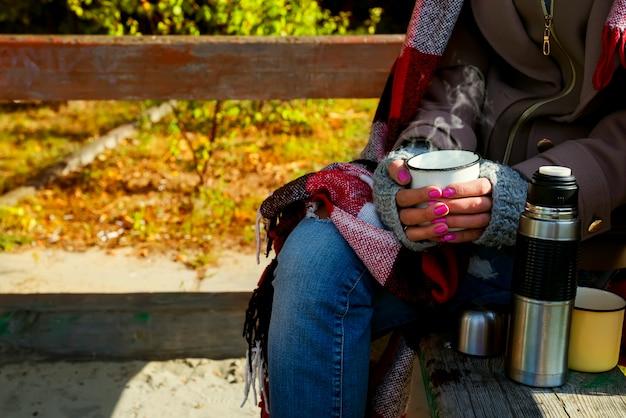 熱いハーブティーのカップを持つ少女