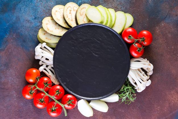 空の石のプレートの周りのおいしい料理やサラダ作りのための新鮮な野菜のトップビュー