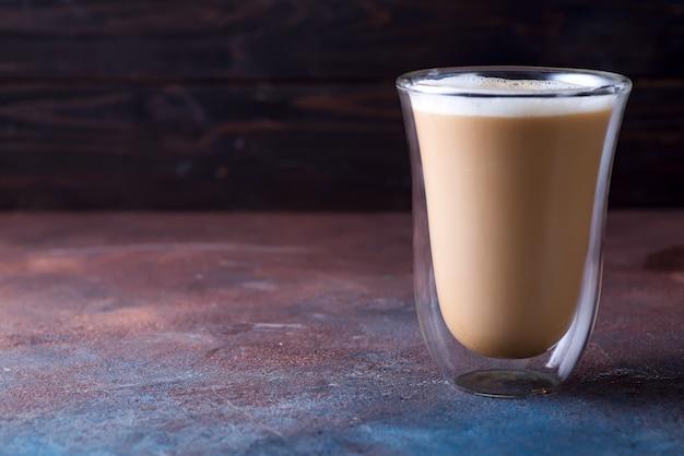 石の暗いテーブルの上のコーヒーカフェラテのガラスカップ