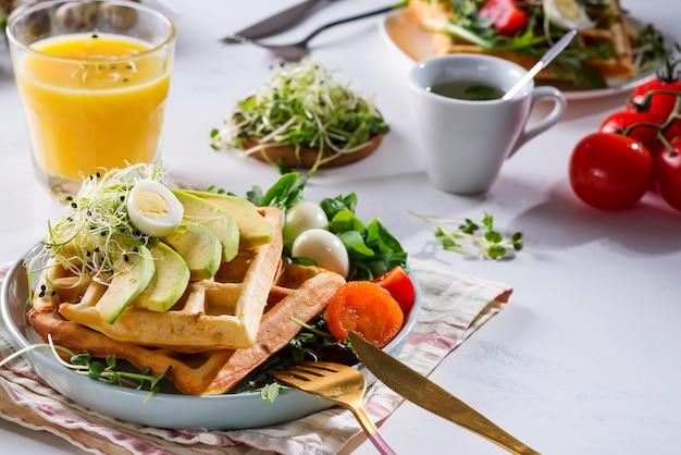 Бельгийские вафли с авокадо, яйцами, микро зеленью и помидорами с апельсиновым соком на мраморном столе