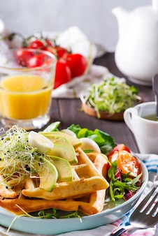 Бельгийские вафли с авокадо, яйцами, микро зеленью и помидорами с апельсиновым соком на деревянном столе