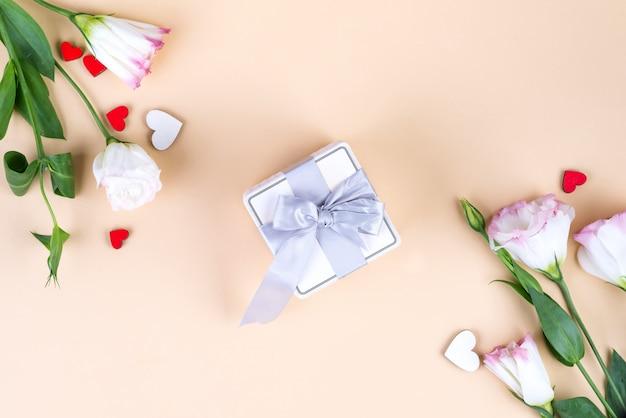 Подарочная коробка и цветы эустомы на день матери или другие праздники на бежевом фоне бумаги