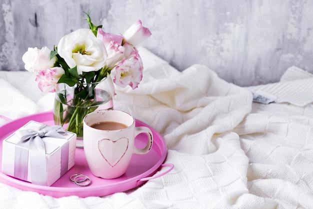 Поднос с чашкой кофе, подарочной коробкой, цветами и кольцами на кровати