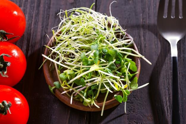 チェリートマトと木の弓で新鮮なタマネギと大根のマイクログリーン