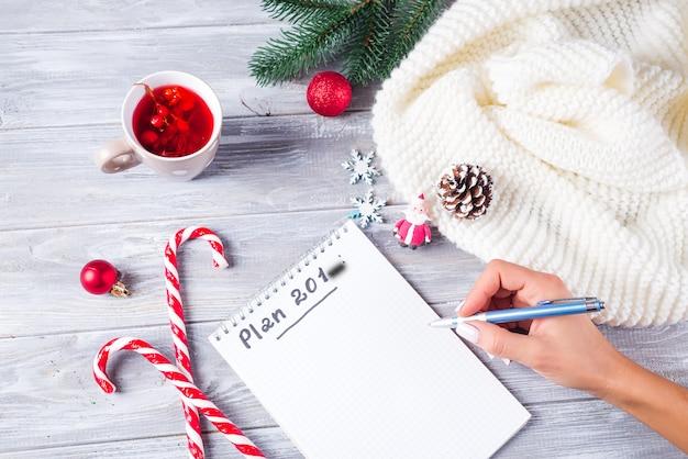 Рука женщины пишет рождественские поздравления