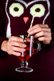 手、クローズアップでおいしいクリスマスグリューワインのガラスカップを保持している女性