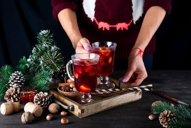 暗い背景に女性の手で木製トレイにフルーツとスパイスのホット自家製ホットワイン