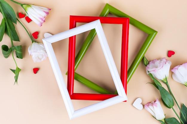 Пустые цветные рамки, красные сердечки и цветы эустомы