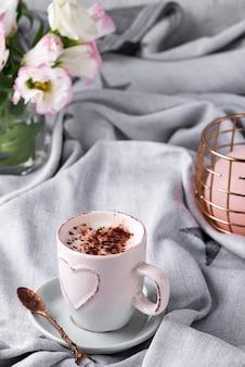 チョコレート、花トルコギキョウ、キャンドル、ベッドで毛布の上にコーヒーのカップを持っています。