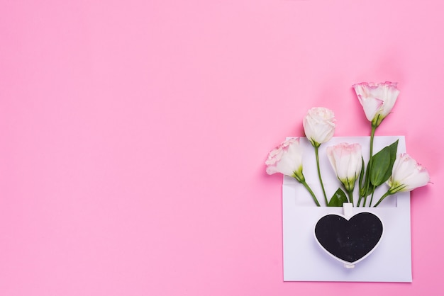 ピンクの背景、トップビューでハートの形の黒板と封筒にトルコギキョウの花と最小限の組成。バレンタインの日グリーティングカード