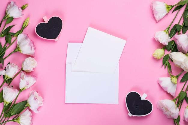 ピンクのトルコギキョウ、エンベロープ、木製の心、フラットレイアウトのフレーム構成。ピンクの背景の花の装飾的なコーナー。