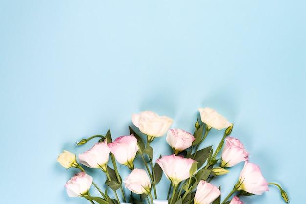青色の背景にピンクのトルコギキョウに咲く花束、フラットレイアウト。バレンタインの日、誕生日、母または結婚式のグリーティングカード