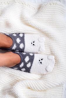 Ноги в носках на вязаном одеяле на кровати,