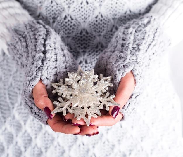 Женские руки держа игрушку снежинки на белизне. праздничный фон для праздников