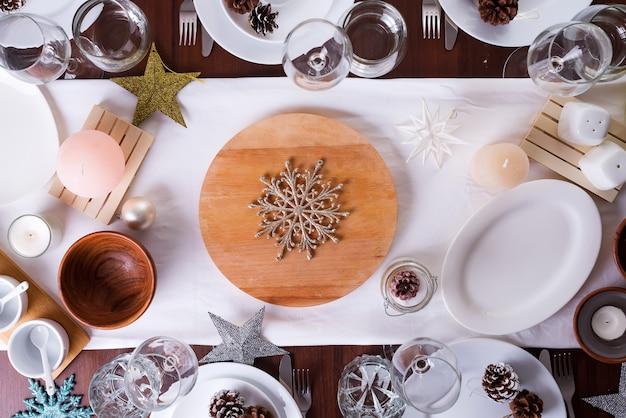 クリスマステーブル設定プレートと暗い木製のテーブルの装飾、フラットレイアウト