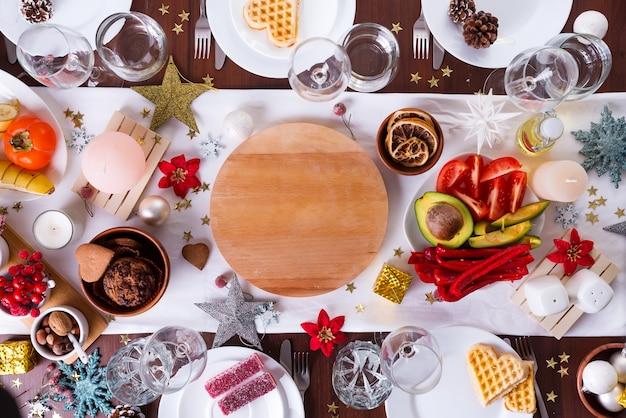 Рождественская сервировка с едой на тарелку и украшения на темный деревянный стол, плоская планировка