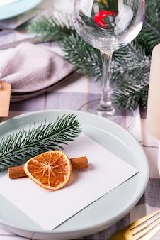 Праздничная сервировка стола рождества и нового года с сухим апельсином и корицей на сером текстиле. столовая украшена