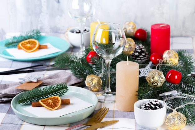 Праздничная сервировка стола рождество и новый год с сухой апельсин и корица на серый текстиль. столовая украшена сосновыми шишками, ветками и свечами