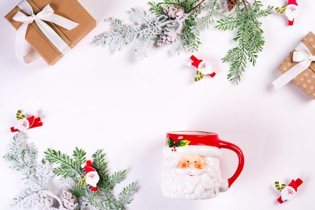 Уютный рождественский праздник. елочные игрушки, зеленые еловые ветки, чашка санта-клауса и подарочная коробка на белом столе. плоская планировка