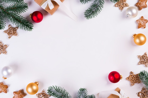 Рождественская и новогодняя праздничная композиция. макет кадр с еловые ветки, подарочная коробка, шары и звезды. плоская планировка, вид сверху праздничный.