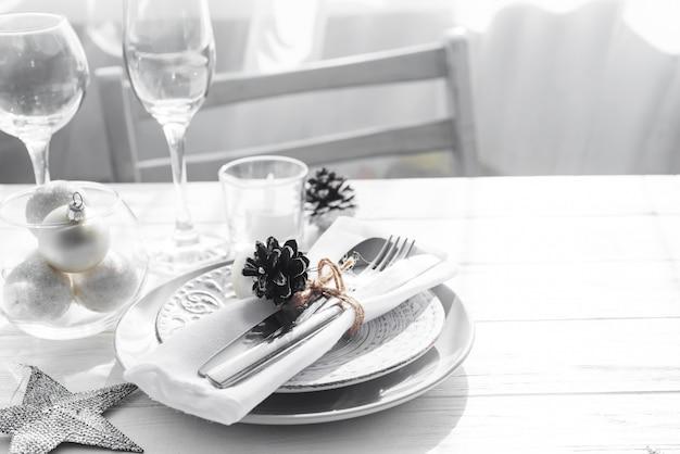 Поставьте сервировку на белый стол с элементами декора рождество. серебряный цвет