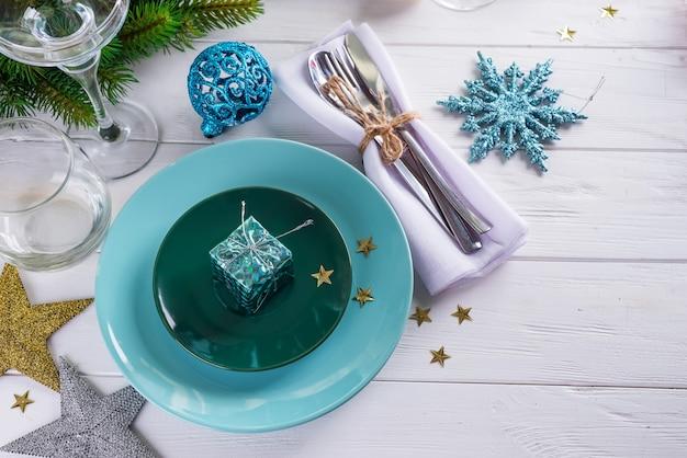Место сервировки стола на рождество белый стол с голубыми элементами декора с зелеными ветками елки