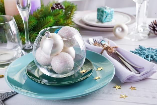 Место сервировки стола на рождество белый стол с синими и серебряными элементами декора с зелеными ветками елки