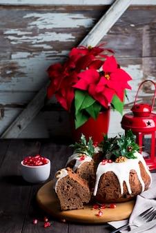 Рождественский нарезанный шоколадный торт с белой глазурью и зернами граната, деревянная темнота с красным фонарем и пуансеттия