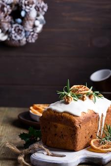 古い木製にアイシング、ナッツ、ドライオレンジをまぶしたフルーツケーキ。クリスマスと冬の休日の自家製ケーキ