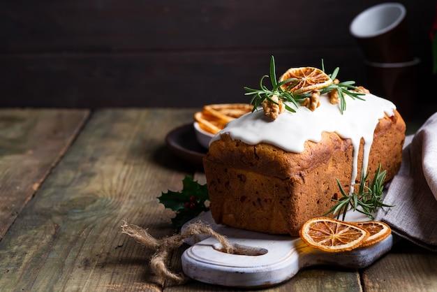 Фруктовый торт, посыпанный глазурью, орехами и сухой апельсин на старое деревянном. рождественские и зимние каникулы домашнего торта