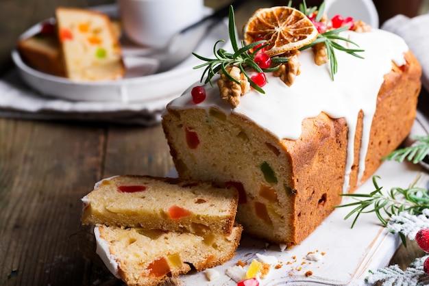 Фруктовый пирог посыпанный нарезкой с глазурью, орехами, зернами граната и сухим апельсином крупным планом. рождественские и зимние каникулы домашнего торта