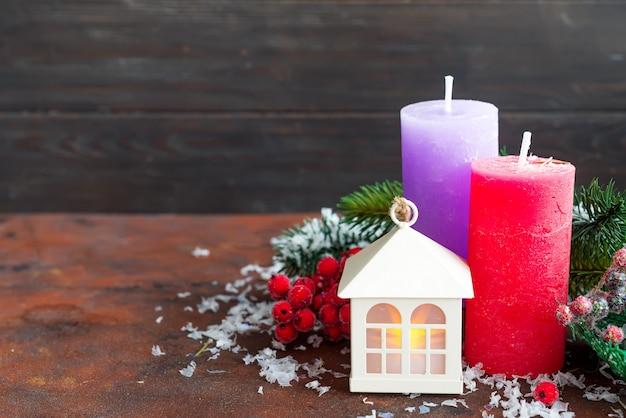 クリスマスライト、キャンドルと石の上のモミの木と小さな家の形のランタン。