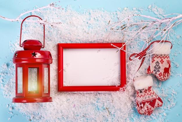 赤いフレーム、赤いランタン、雪の枝、雪の青のミトンクリスマスグリーティングカード