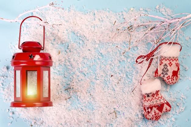 赤いランタン、雪の枝、雪の青のミトンクリスマスグリーティングカード