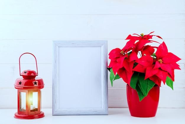 白いフレーム、植木鉢のポインセチア、白い木の上の赤いランタンとモックアップの写真