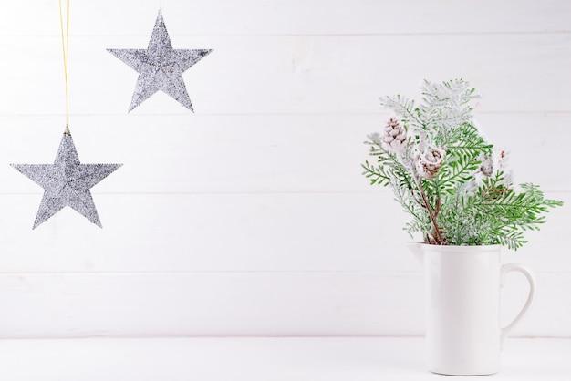 花瓶の松の枝、白い木の星が付いているスペースをコピーします。